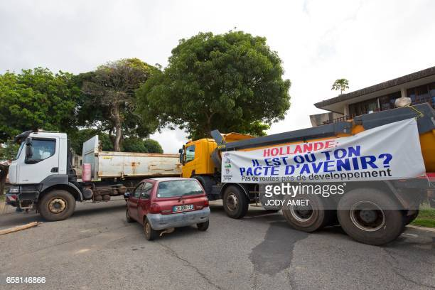 Trucks form a blockade in Cayenne on March 26 with a banner reading 'Hollande where is your deal on the future No roads no development' French Guiana...