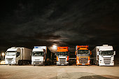 Five different trucks parked in the night, under the full moon
