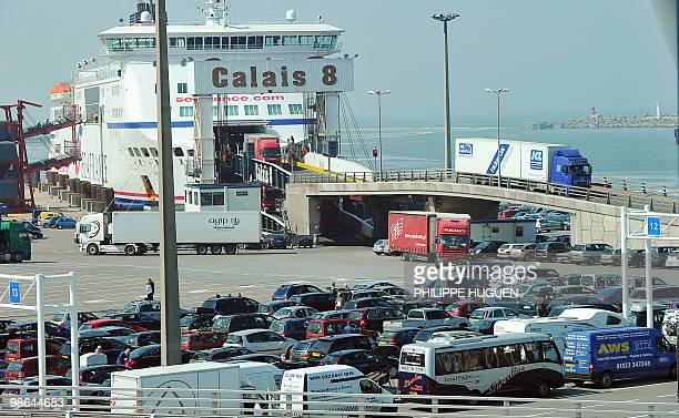 Trucks leave a ferry from Dover while passengers cars queue on April 17 at the Calais harbour northern France as Britain has extended a ban on most...