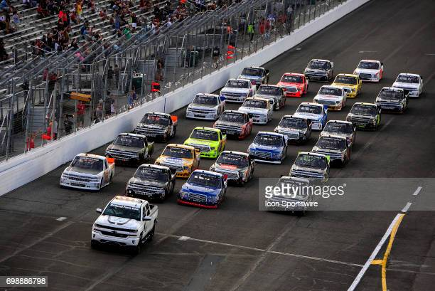 Trucks line up four wide to salute the fans one the pace laps just before the start of the NASCAR Camping World Truck Series Drivin' for Linemen 200...