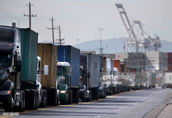 Trucks line up to enter a berth at the Port of Oakland on February 11 2015 in Oakland California A work slowdown at West Coast ports continues amidst...