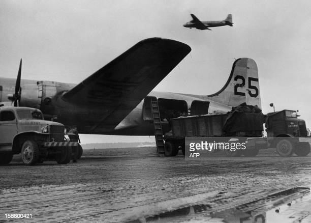 Trucks are loading planes which are used during the famous Berlin Airlift during the Berlin occidental zone blockade by Russia in June 1948 in...