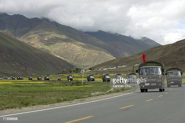 Trucks of the Chinese army carry goods along the QinghaiTibet road next to the QinghaiTibet Railway on June 29 2006 in Dangxiong County Tibetan...