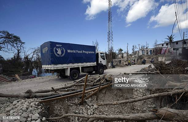 Trucks of the UN's World Food Programme arrive in Port Salut southwest of PortauPrince on October 12 following the passage of Hurricane Matthew The...
