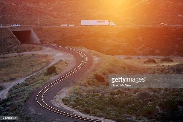 Trucks on Interstate 15 in Cajon Canyon pass railroad tracks near the San Andreas Fault at sunrise on July 1 2006 near San Bernardino California The...