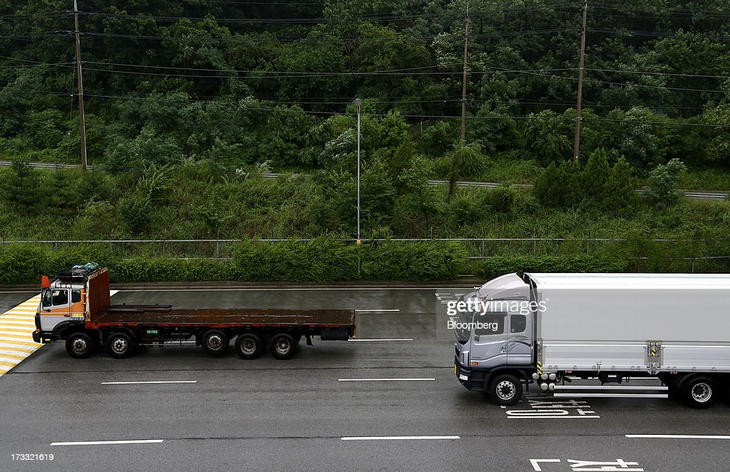 Trucks pass the Customs, Immigration and Quarantine (CIQ) office as they travel toward the Gaeseong Industrial Complex on a road, linked to North Korea, near the demilitarized zone (DMZ) in Paju, South Korea, on Friday, July 12, 2013. North Korea notified South Korea today that it has deferred two separate sets of talks on the tours and the family reunions it proposed yesterday, and said it wants to focus on the ongoing dialog to reopen the joint Gaeseong industrial zone, the Souths Unification Ministry said in an e-mailed statement. The two sides yesterday decided to hold talks in Gaeseong on July 15, which will be their third round in one week, on normalizing operations in Gaeseong after the North unilaterally recalled its workers in April. Photographer: SeongJoon Cho/Bloomberg via Getty Images