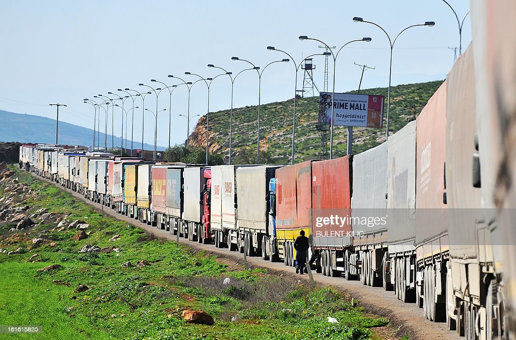 Trucks queue at the Cilvegozu border crossing between Turkey and Syria near Hatay on February 13, 2013 in the vicinity of the site where a vehicle exploded on February 11 in the buffer zone between Turkey and Syria. Fourteen people died in the blast.
