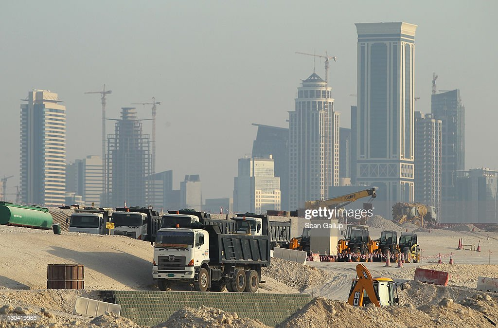 Trucks stand at a construction site across from skyscrapers in the budding new financial district on October 26 2011 in Doha Qatar Qatar which is...