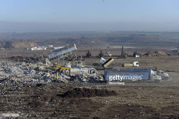 Trucks stand in a landfill cell at the Melbourne Regional Landfill site operated by Cleanaway Waste Management Ltd in Ravenhall Victoria Australia on...