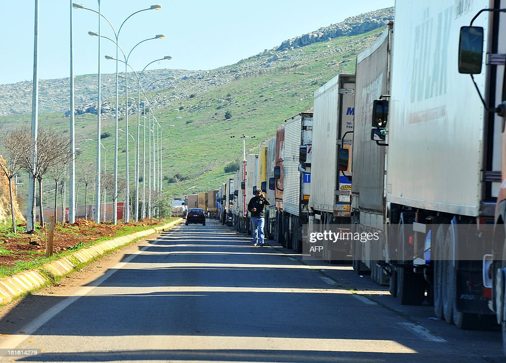 Trucks wait at the Cilvegozu border crossing between Turkey and Syria near Hatay on February 13, 2013 in the vicinity of the site where a vehicle exploded on February 11 in the buffer zone between Turkey and Syria. Fourteen people died in the blast.