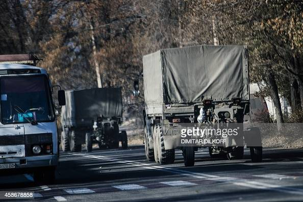 Trucks without license plates tow a 122mm howitzer artillery piece on November 9 2014 through Makiivka Artillery fire rocked east Ukraine's rebel...