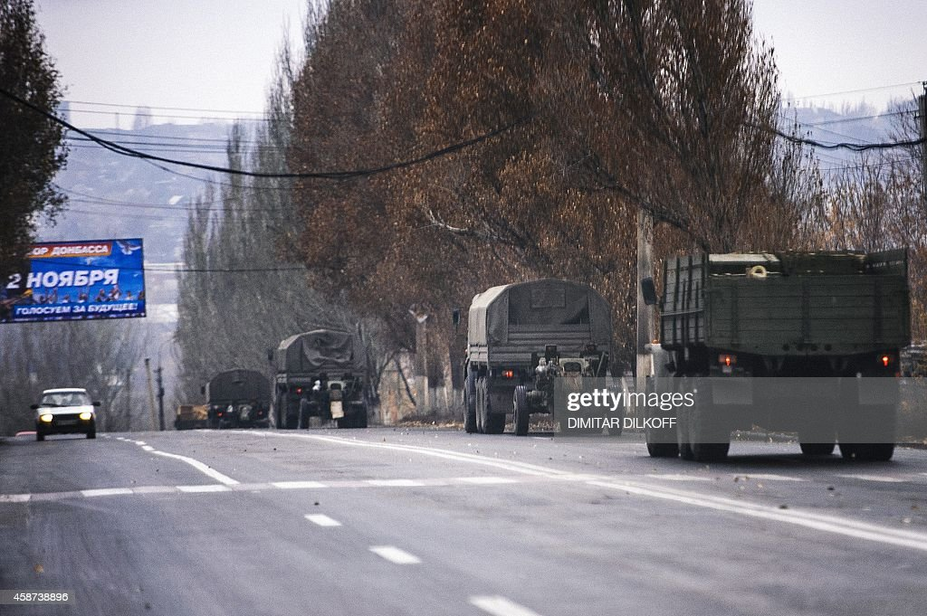 Trucks without license plates tow a 122mm howitzer artillery piece on November 10 2014 through Makiivka New unidentified armored columns rumbled...