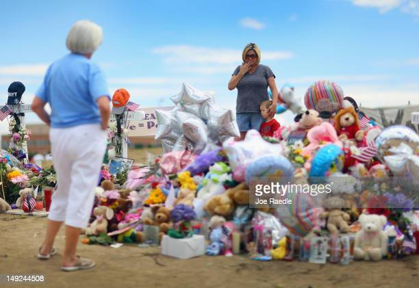 Trudy Stevens stands with her son Gavin Stevens as they visit a makeshift memorial setup across the street from the Century 16 movie theatre where...