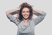 Attractive young smiling woman holding hands in hair and keeping eyes closed while standing against grey background