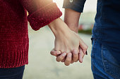 Cropped shot of a couple holding hands outdoors