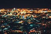 True tilt shift shooting of residential district and industrial zone in night metropolis from high point: multiple residential houses, teal and orange lights from windows, strong bokeh in foreground
