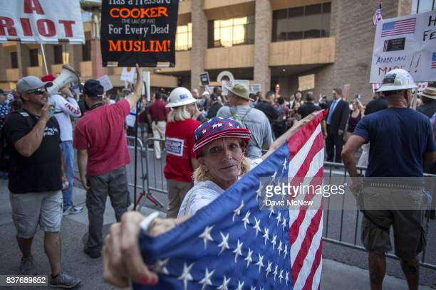 Trump supporter holds a flag prior to the start of a rally by President Donald Trump at the Phoenix Convention Center on August 22 2017 in Phoenix...
