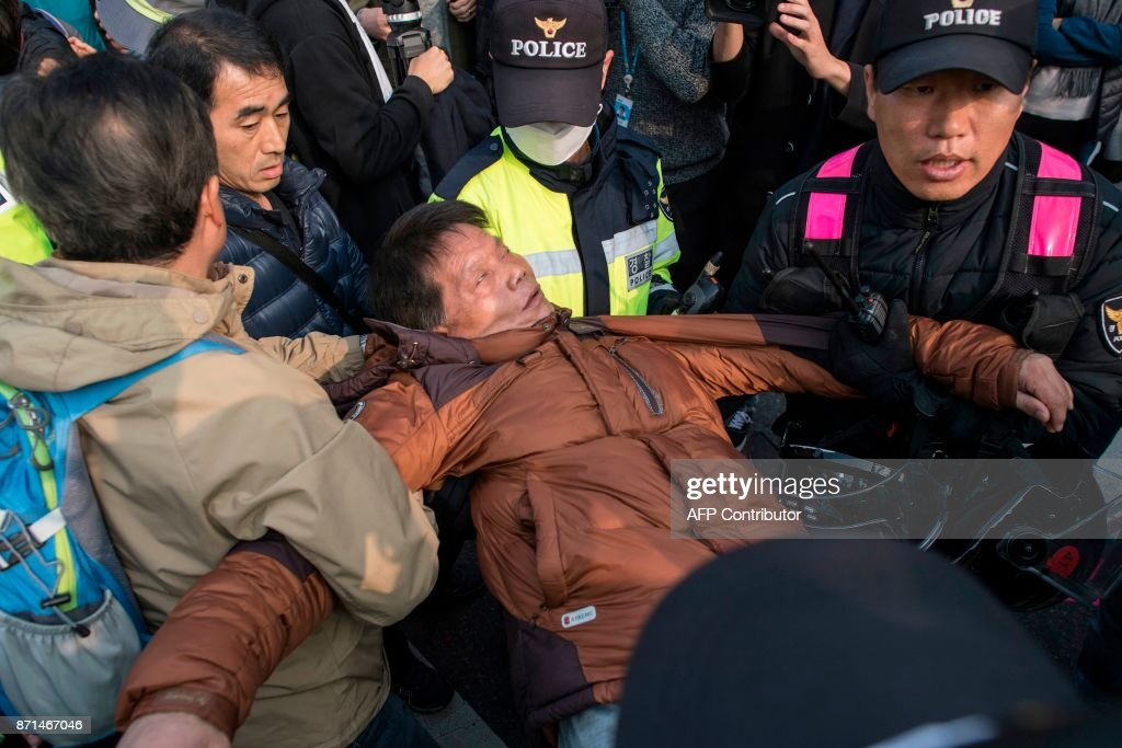 A Trump supporter is treated by police after attempting to disrupt an anti-Trump protest during a rally outside the National Assembly in Seoul on November 8, 2017. US President Donald Trump offered North Korean leader Kim Jong-Un what he called 'a path towards a much better future' as tensions soar over Pyongyang's nuclear ambitions. / AFP PHOTO / Ed JONES