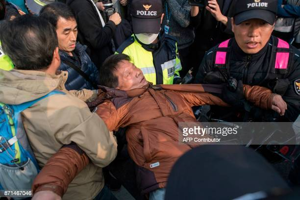 A Trump supporter is treated by police after attempting to disrupt an antiTrump protest during a rally outside the National Assembly in Seoul on...