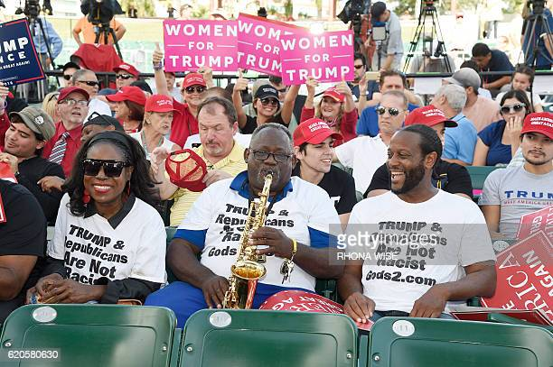 A Trump supporter plays the saxophone prior to a rally for Republican presidential nominee Donald Trump in Miami Florida on November 2 2016 Hillary...