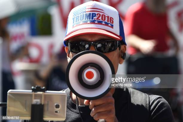 A Trump supporter speaks into a megaphone to address people demonstrating against Breitbart News and what the protestors describe as the media...
