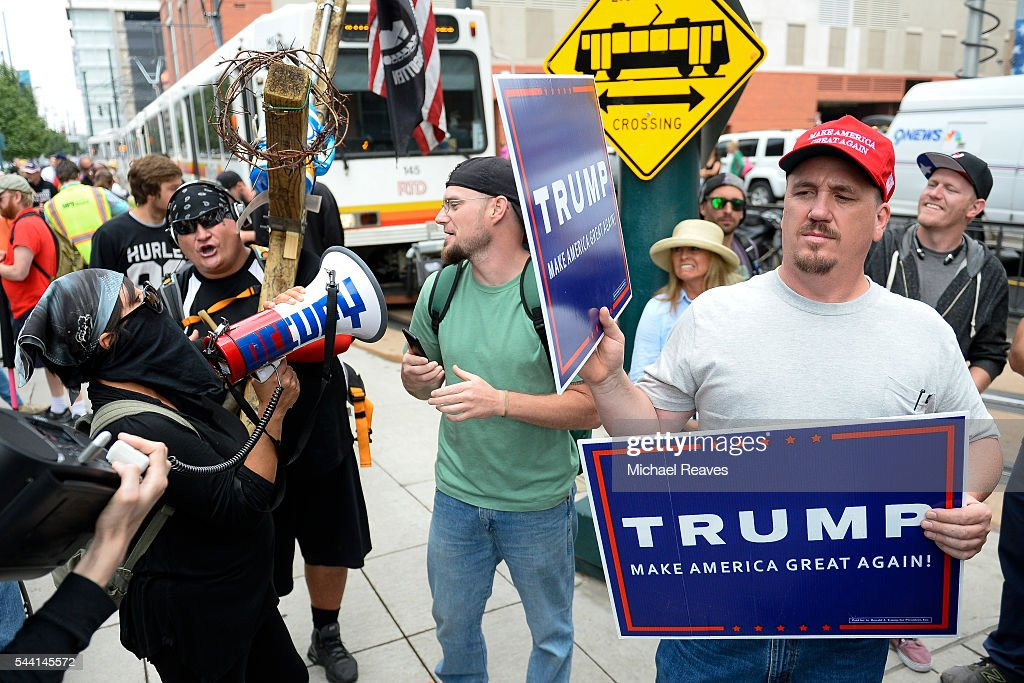 A Trump supporter uses a sign to block music playing from a anti-Trump protestor outside the Western Conservative Summit on July 1, 2016.