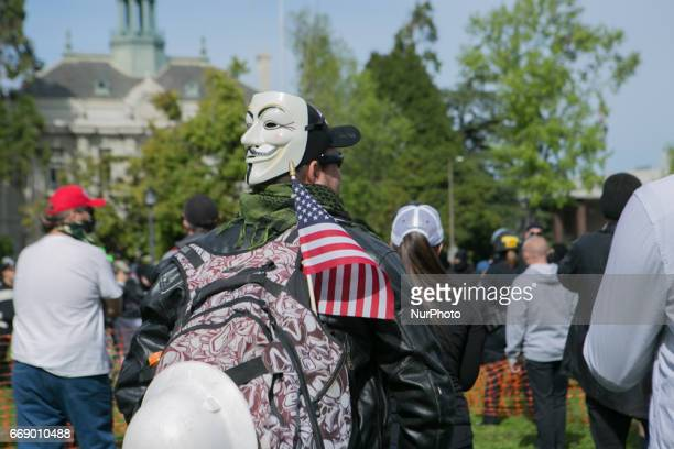 A Trump supporter wears a Guy Fawkes mask during a free speech rally at Martin Luther King Jr Civic Center Park in Berkeley California United States...