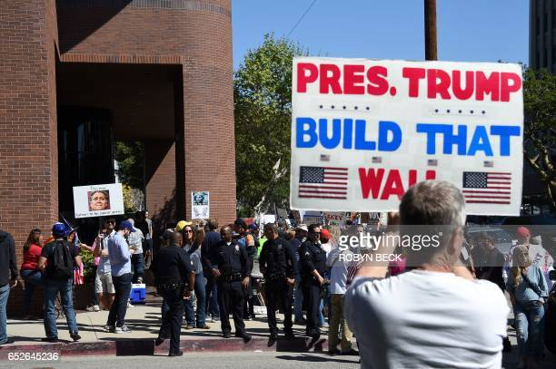 A Trump supporter with a sign reading 'Pres Trump Build That Wall' faces people demonstrating against Breitbart News and what the protestors describe...