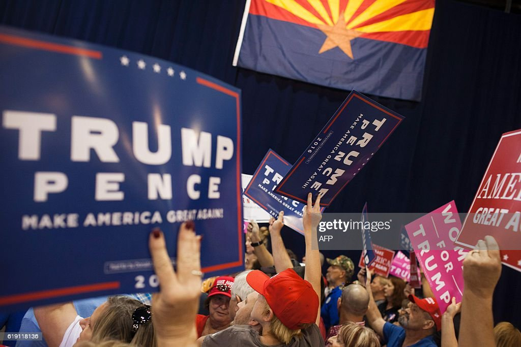 Trump supporters arrive at Republican Presidential nominee Donald Trump rally at the Convention center in Phoenix, Arizona on October 29, 2016. America's top cop FBI Director James Comey found himself center stage Saturday as his renewed probe of Hillary Clinton's emails set a bitter tone for the final ten-day stretch of the campaign. Both Clinton and her Republican rival Donald Trump piled pressure on Comey to put his cards on the table and end speculation about the investigation before America goes to the polls on November 8. / AFP / Caitlin O'Hara