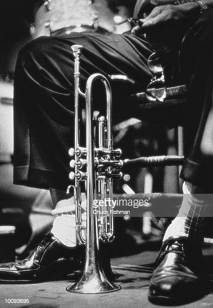 Trumpet between jazz player's legs, low section (B&W)