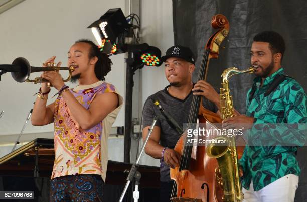 Trumpet player Theo Croker bassist Eric Wheeler saxophonist Anthony Ware perform at the Newport Jazz Festival August 6 2017 in Newport Rhode Island...