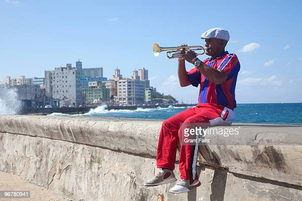 trumpet playing man playing by sea wall