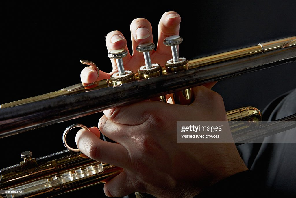 trumpet with fingers on keys, close-up : Stock Photo