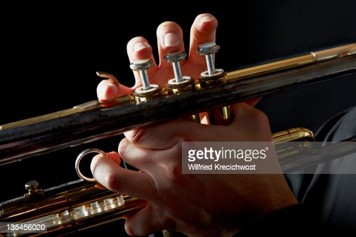 trumpet with fingers on keys, close-up