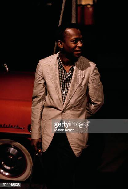 Trumpeter Miles Davis leaning on a car outside of jazz club Cafe Bohemia in New York City in 1956