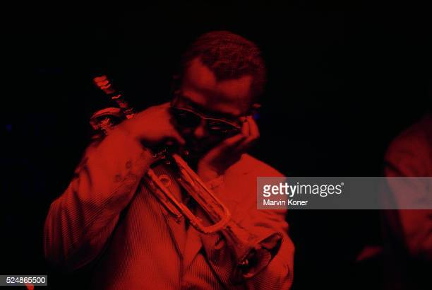 Trumpeter Miles Davis plugging his ears while performing at jazz club Cafe Bohemia in New York City in 1956