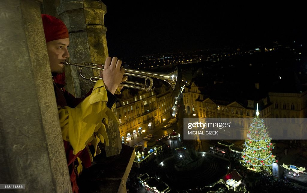 A trumpeter plays from the Old Town tower in front of the traditional Christmas tree placed at the traditional Christmas market on December 17 , 2012 at the Old Town Square, in Prague.