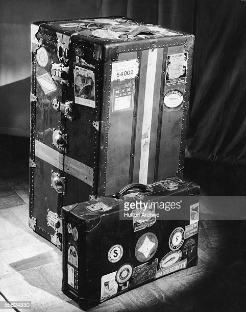 A trunk and suitcase both covered with travel stickers circa 1950
