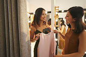 Female boutique owner giving dress to the woman in fitting room
