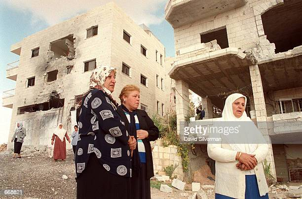 Tsafira alHannesh right is joined by her neighbors outside her family's and her neighbor's damaged homes November 1 2000 in the West Bank town of...