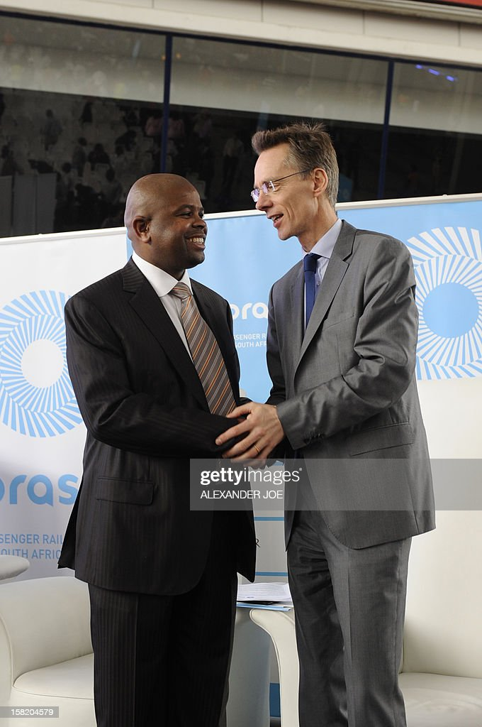 Tshepo Lucky, Montana Group Chief Executive Officer (CEO) of Passenger Rail Agency of South Africa (PRASA) shakes hands in Johannesburg on December 11, 2012 with Andreas Knitter senior Vice President of Alstom, the French company that won the tender to build South African new commuter trains that will start running in 2015. AFP PHOTO / ALEXANDER JOE