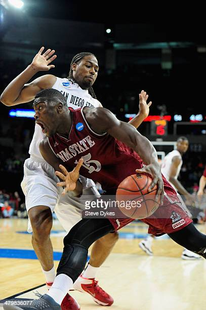 Tshilidzi Nephawe of the New Mexico State Aggies drives the ball around Josh Davis of the San Diego State Aztecs during the second round of the 2014...