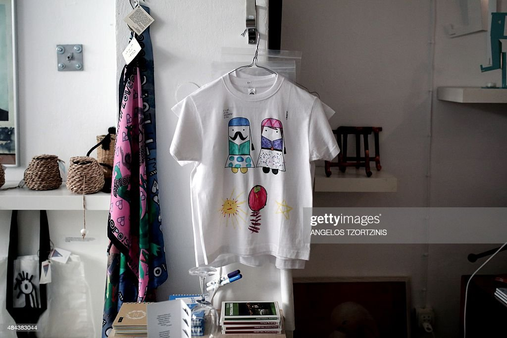 A tshirt hangs for sale depicting an Evzon a member of the Greek Presidential Guard and a woman wearing a traditional Greek costume are seen at the...
