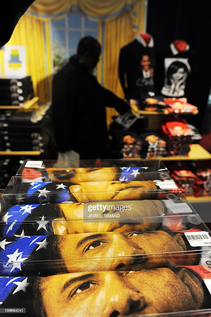 T-shirts featuring images of US President Barack Obama and First Lady Michelle Obama are displayed at a gift shop in Washington, DC, on January 18, 2013. Crowds may be smaller on January 21 inauguration than when Barack Obama was first sworn into office in 2009, but security is as tight as ever, with experts warning a 'lone wolf' would pose the greatest threat. Between 500,000 and 800,000 people are expected to pass through the National Mall, the immense greenway that leads up to the Capitol, compared to the 1.8 million spectators who came to applaud Obama four years ago. AFP PHOTO/Jewel Samad