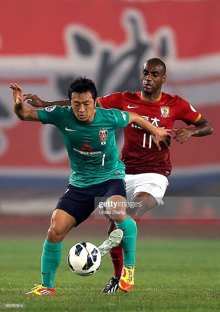 Tsukasa Umesaki (L) of Urawa Red Diamonds challenges Da Conceicao Silva Luiz Guilherme of Guangzhou Evergrande during the AFC Champions League Group F match between Guangzhou Evergrande and Urawa Red Diamonds at Tianhe Stadium on February 26, 2013 in Guangzhou, China.