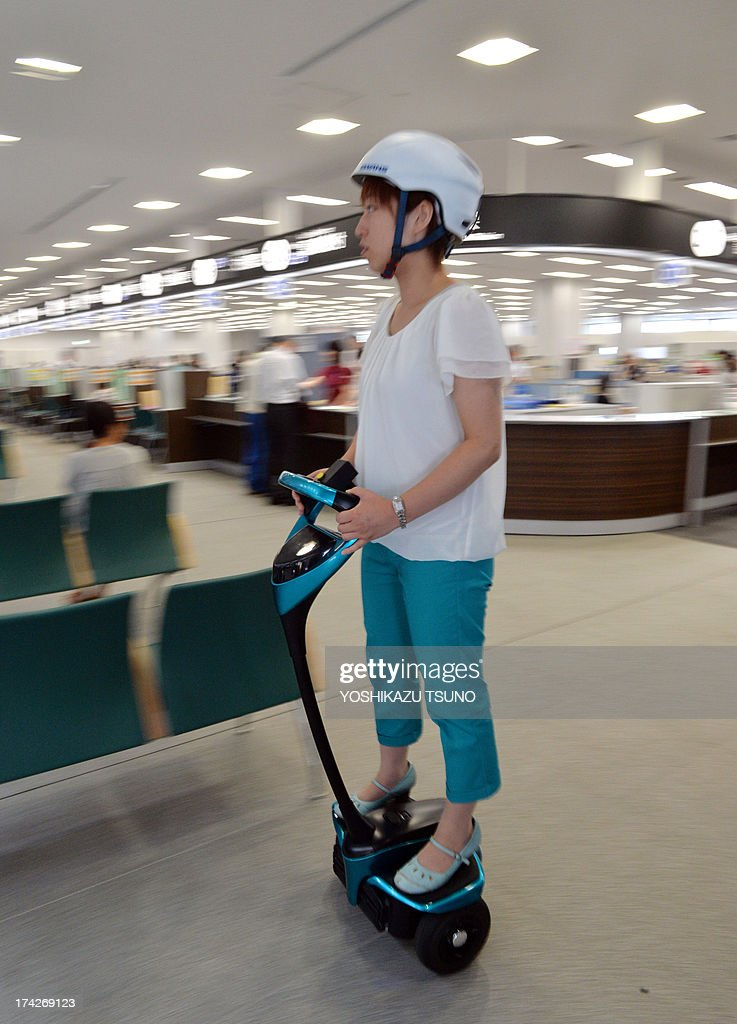 A Tsukuba City Hall employee rides on Toyota's transport assistance robot, called the 'Winglet', during a demonstration in City Hall in Tsukuba City, suburban Tokyo on July 23, 2013. Toyota and Tsukuba City started to field test the next generation of 'personal mobility robot' on the public thoroughfare, with trial runs scheduled until 2016. AFP PHOTO / Yoshikazu TSUNO