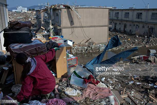 Tsunami survivor Ran Sasaki collects her belongings in her destroyed house in Ishinomaki Miyagi prefecture on April 10 2011 Prime Minister Naoto Kan...