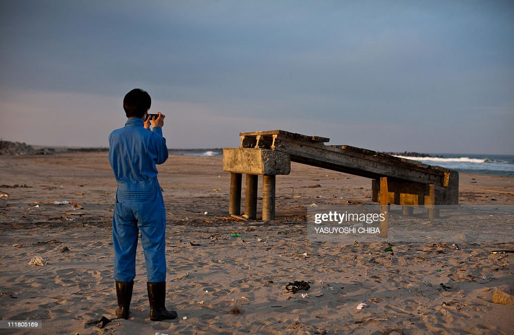 A tsunami survivor takes pictures of a concrete incline slope for cars from a breakwater left on a beach by the March 11 tsunami, in Sendai in Miyagi prefecture on April 7, 2011. Armed with radiation meters and protective gear, police launched an intensive search on April 7 for people missing inside the exclusion zone around Japan's disaster-stricken nuclear power plant.