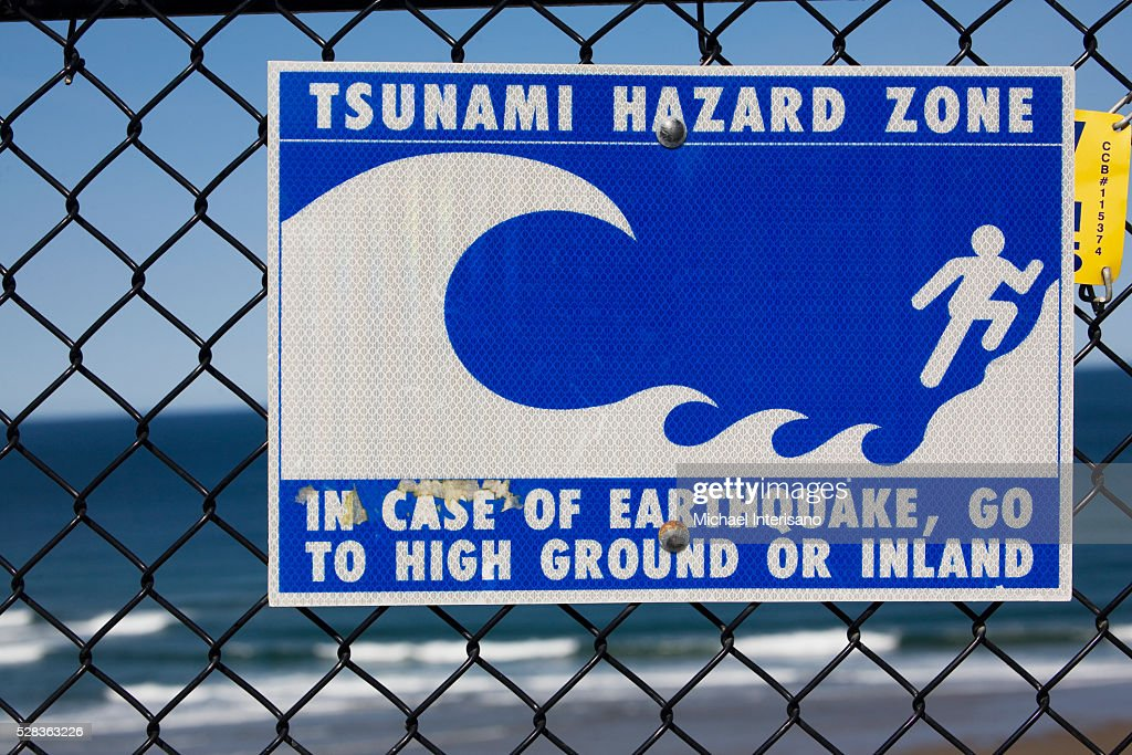 Tsunami Warning Sign On A Fence With The Ocean In The Background; Lincoln City Oregon United States Of America