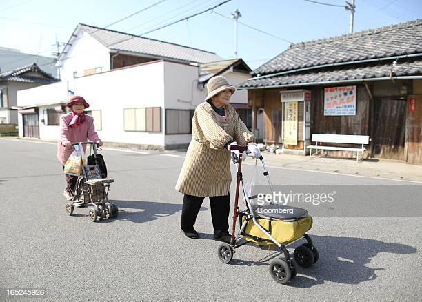 Tsutako Hashimoto right and Kiku Sakakibara stroll down a road on Gogo Island in Matsuyama Ehime Prefecture Japan on Friday March 22 2013 A...